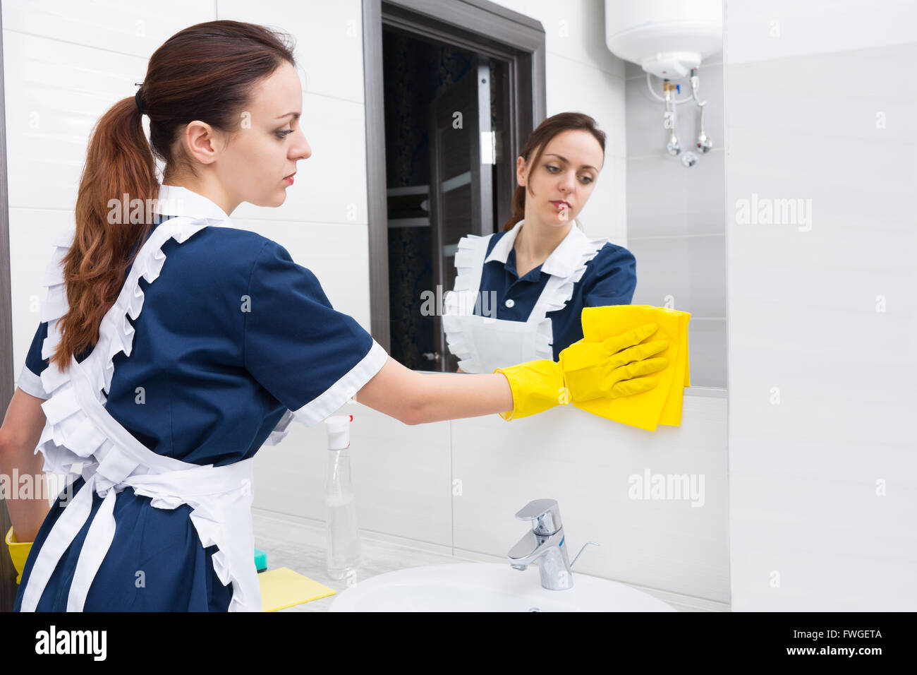 Single young adult female hotel maid using yellow cloth and rubber gloves to tidy up low section of mirror in bright - Stock Image