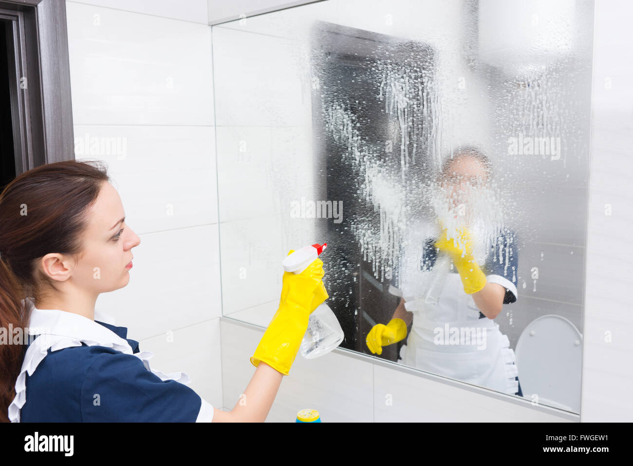 Housekeeper cleaning a wall mirror in a bathroom spraying it with detergent, close up side view with reflection - Stock Image