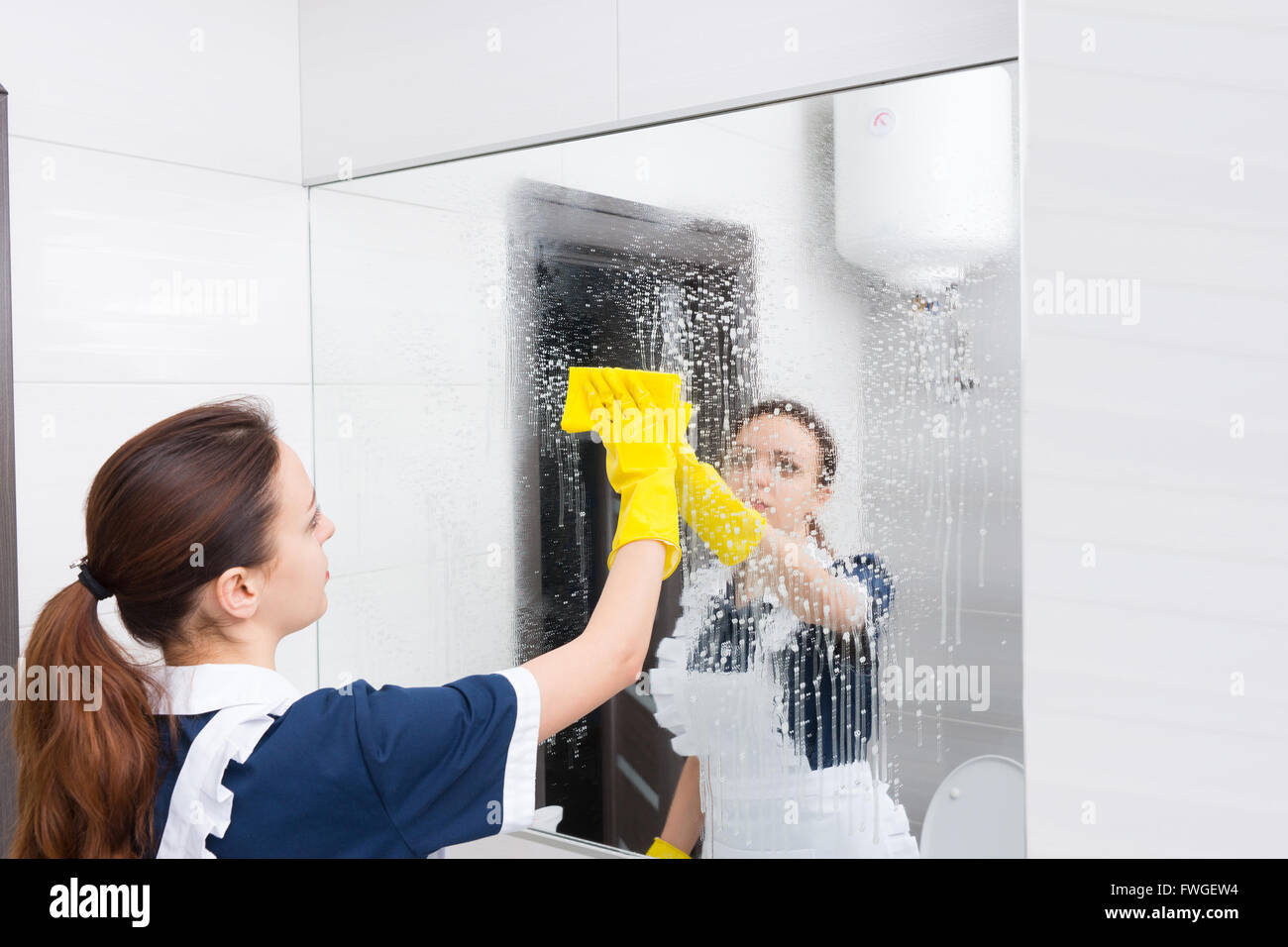 Housekeeper or maid cleaning a large wall mirror in a white bathroom wiping it with a cloth after spraying it with - Stock Image
