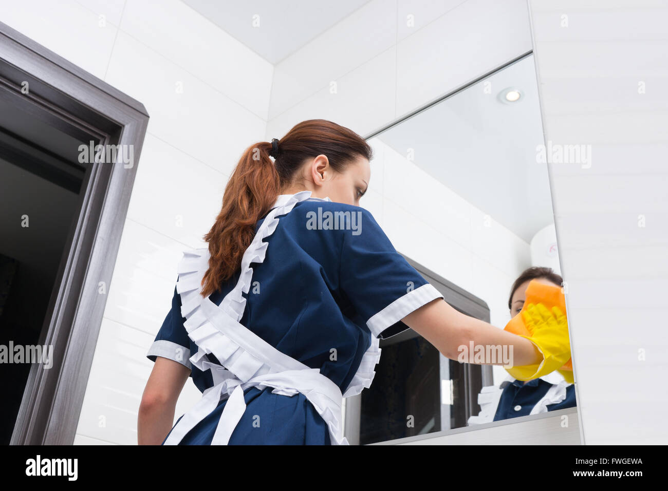 Low angle view on maid in blue and white uniform in rubber gloves cleaning large bathroom mirror - Stock Image