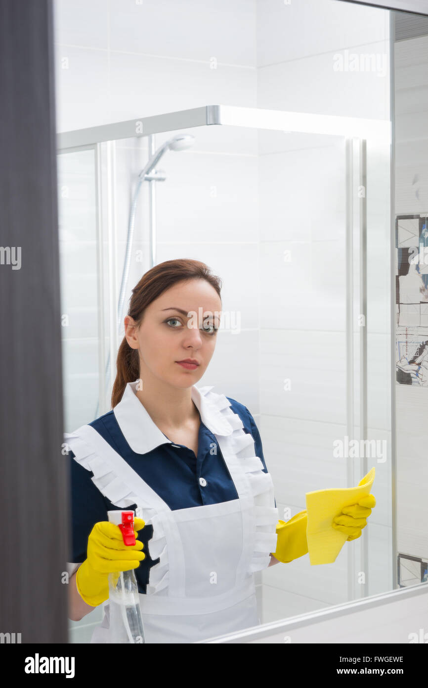 Single cute young maid with serious expression looking in mirror while holding clear spray bottle and cloth in yellow - Stock Image