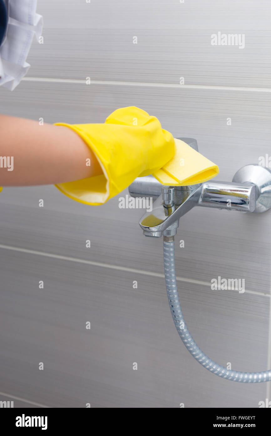 Maid or housewife cleaning the tap in a shower with her gloved hands and a soft absorbent cloth, cloth up view Stock Photo