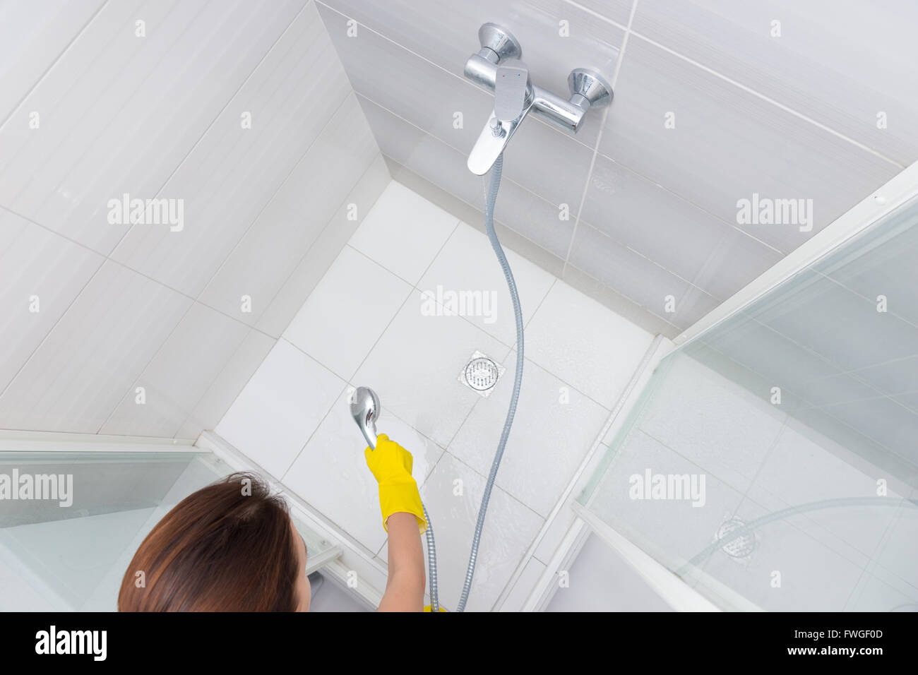 Housekeeper rinsing the white tiles on a shower cubicle as she Stock ...