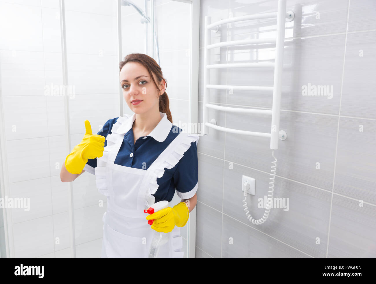 Confident young female domestic worker standing in blue dress and white apron with thumbs up gesture while holding spray bottle next to shower stall in bathroom. Stock Photo