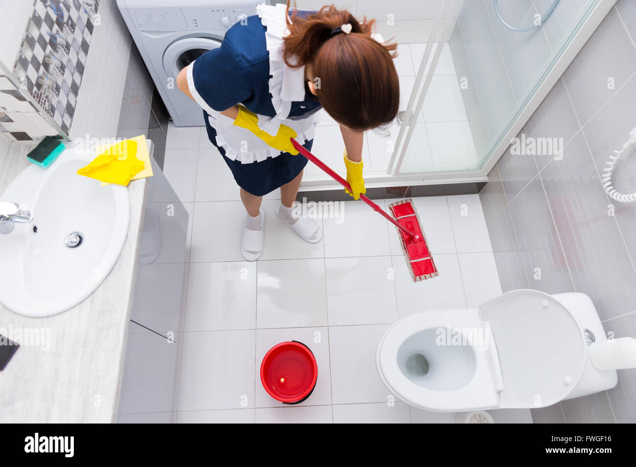 Housekeeper In A Hotel Mopping A Floor In A Clean White