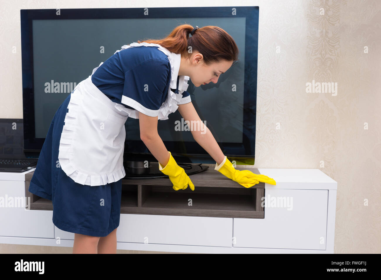 Housekeeper, maid or char in a neat uniform and white apron dusting a television and cabinet in a home or hotel - Stock Image