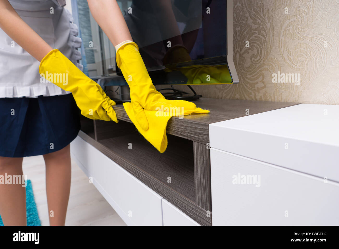 Housekeeper cleaning and dusting a television cabinet with a colorful yellow cloth, close up of her hands in yellow - Stock Image