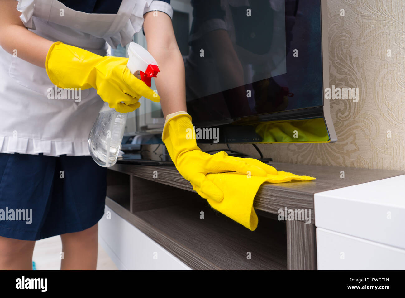 Maid cleaning a television cabinet spraying it with detergent before wiping it with a cloth, close up on her gloved - Stock Image
