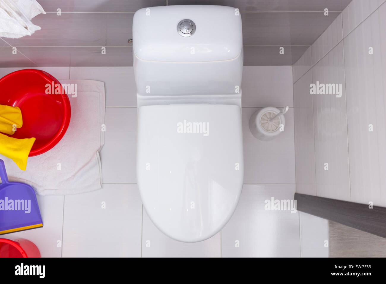 Overhead view of a closed toilet in a white and grey tiled bathroom ...