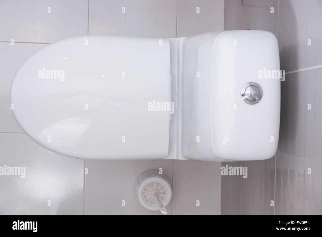 Close up overhead view of a plain white toilet with the seat shut and a  toilet