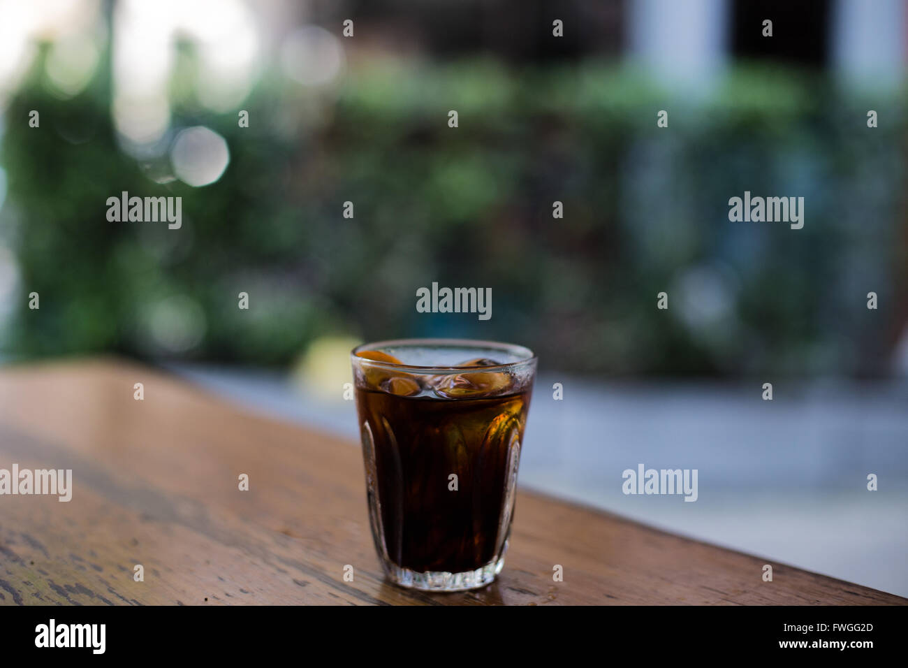 Cold brew iced coffee on wooden table with blurry background - Stock Image