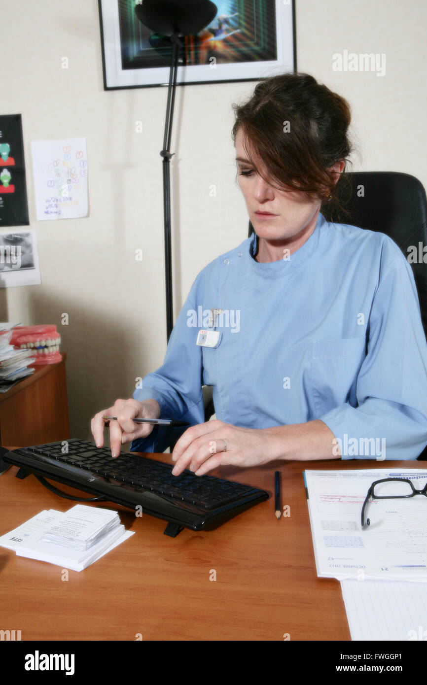 Woman doctor writing in a computer in her office - Stock Image