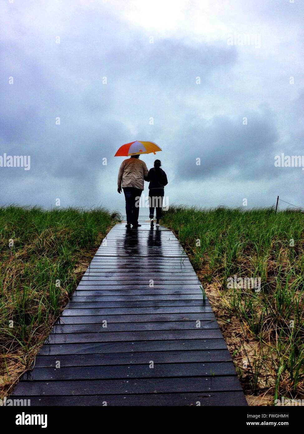 Rear View Of Couple Walking On Boardwalk - Stock Image