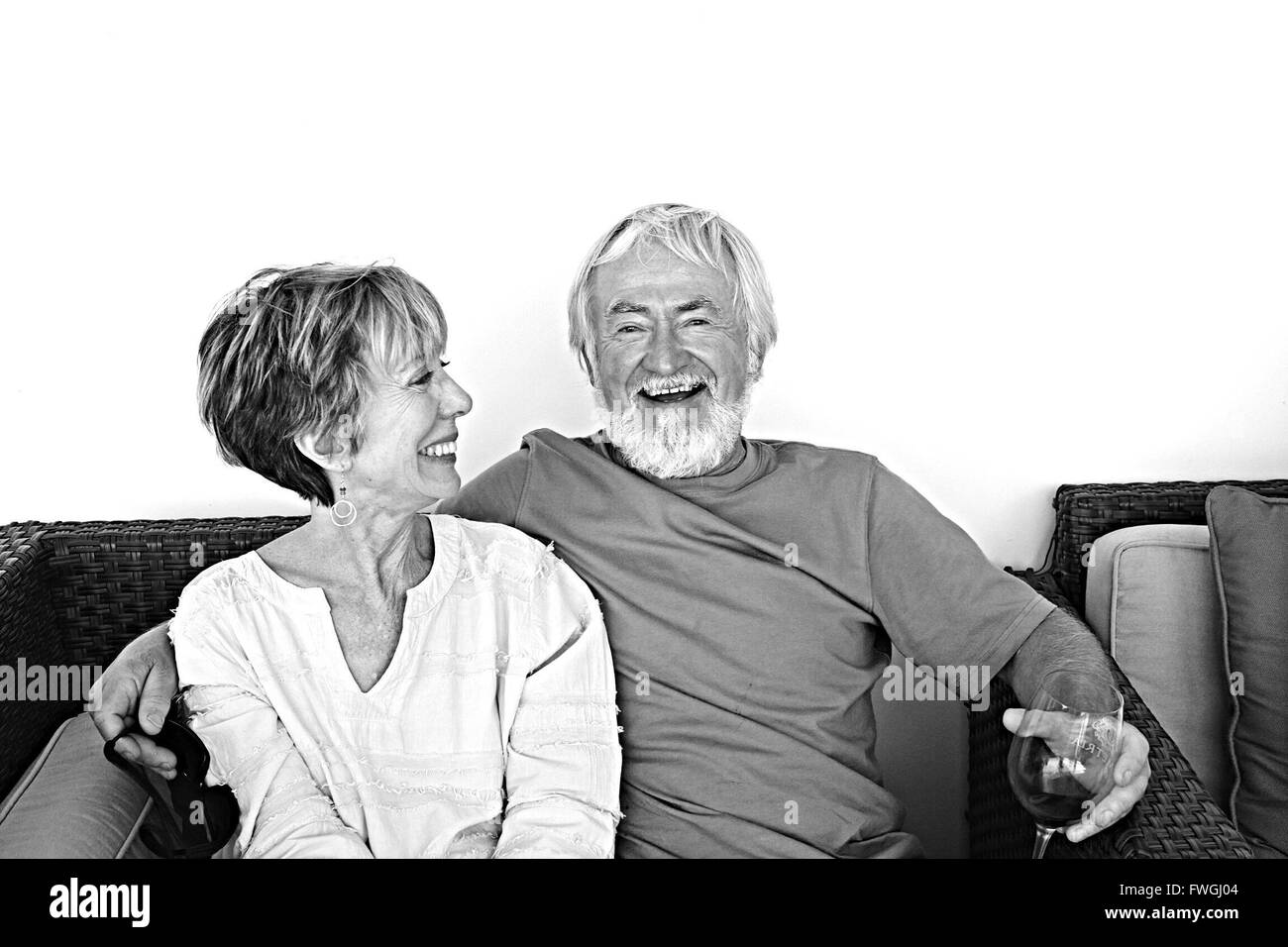 Happy Senior Couple Sitting On Sofa At Home - Stock Image