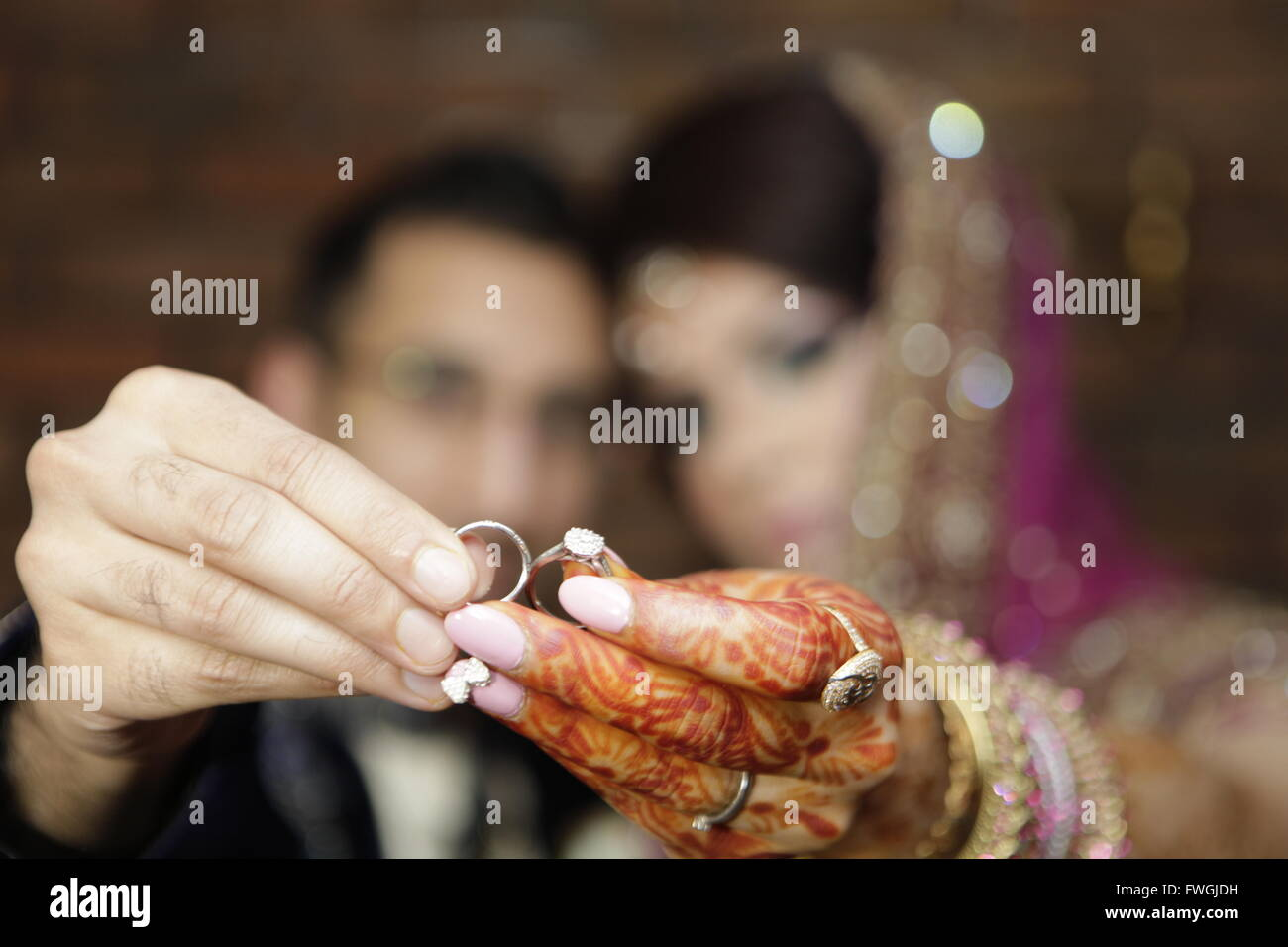 Close Up Of Couple Holding Wedding Rings In Hand Stock Photo