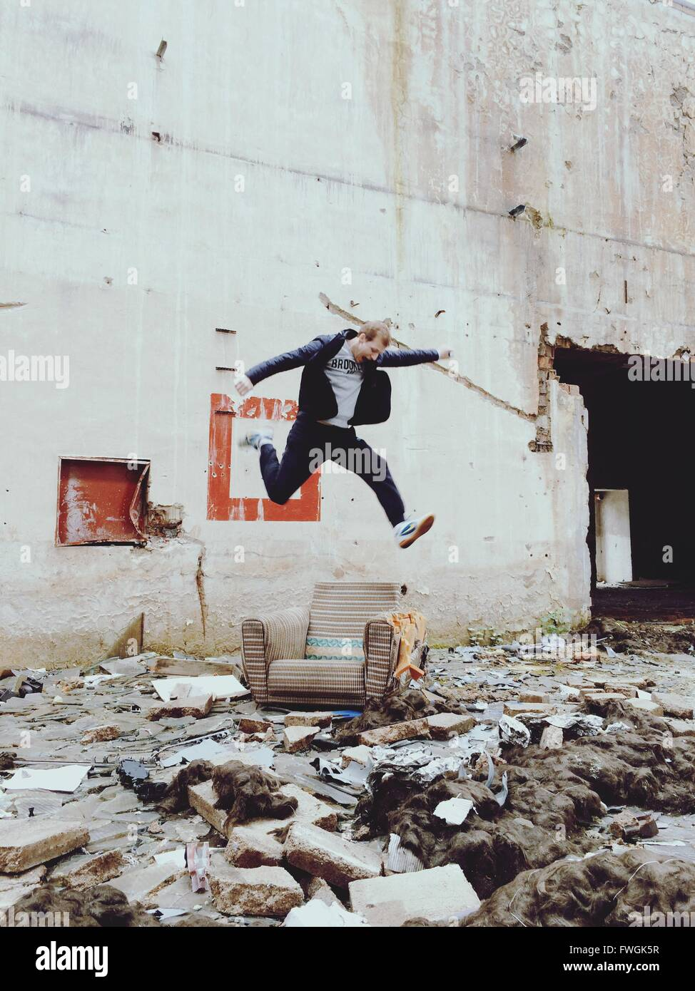 Young Man Jumping Over Chair Outside Abandoned Building - Stock Image