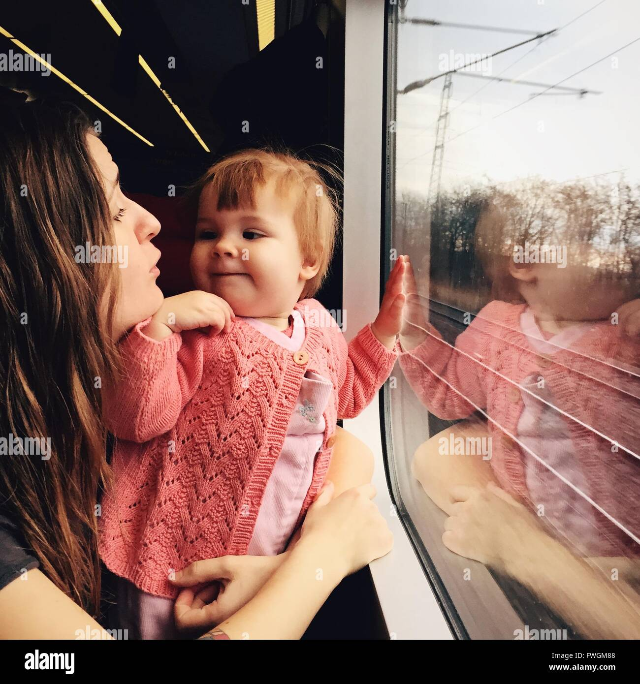 Baby With Mother In Train - Stock Image