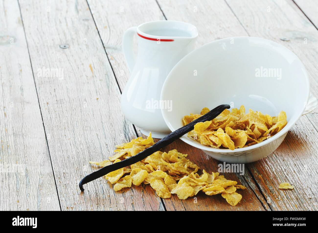 High Angle View Of Vanilla Pod On Corn Flakes Bowl By Milk On Table - Stock Image