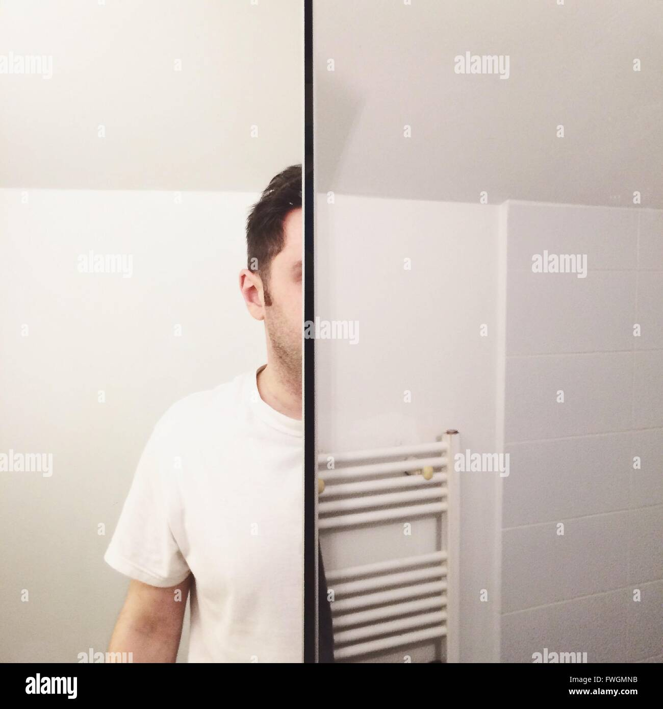 Cropped Image Of Man Reflecting On Mirror Against Wall At Bathroom - Stock Image