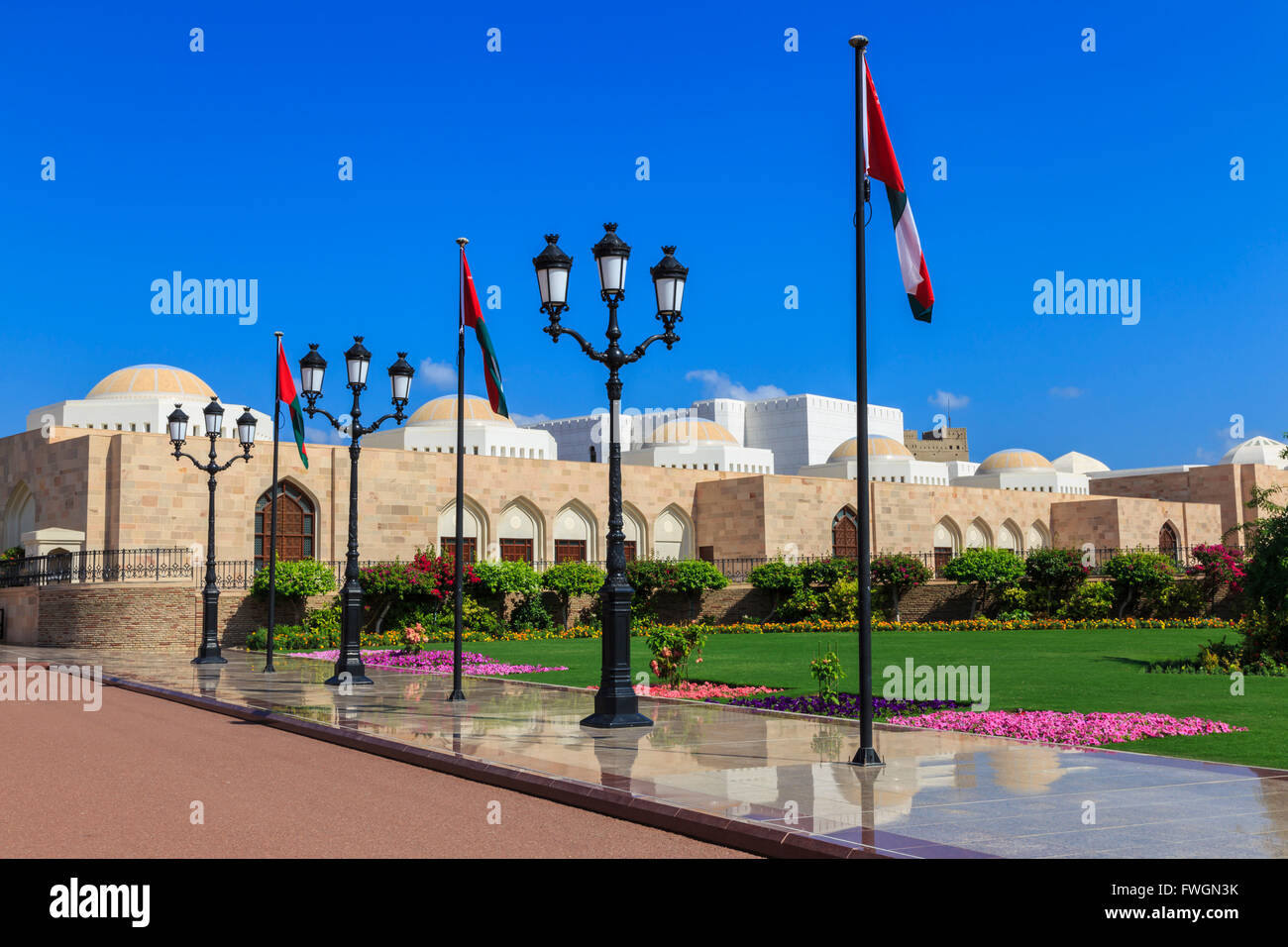 Polished pavements, National Flags, lush lawns and flowers in bloom, Sultan's Palace, Old Muscat, Oman, Middle - Stock Image