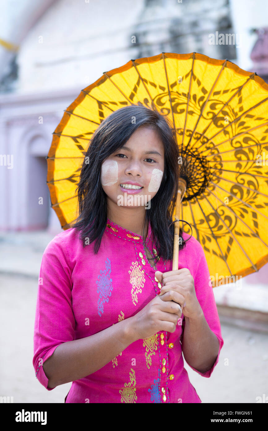 A local girl with a traditional paper sunshade umbrella and thanaka face paint, Monywa, Sagaing, Myanmar (Burma), - Stock Image