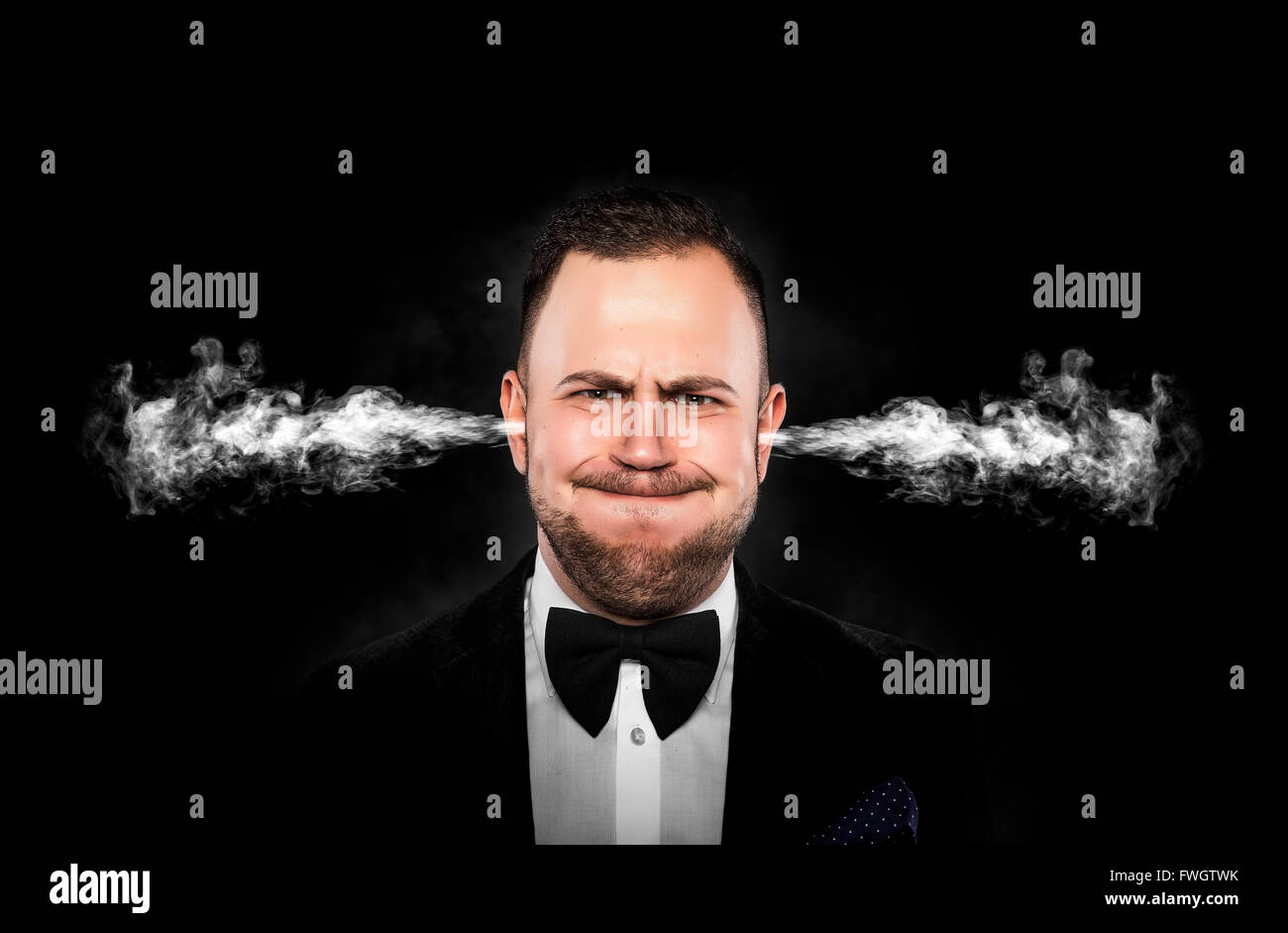 Stressful man with smoke or fume coming out from his ears on dark background. - Stock Image