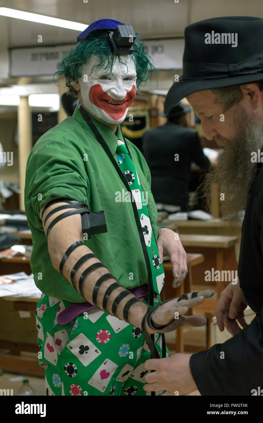 An Orthodox rabbi puts phylacteries on a Jewish New York City character who dresses like the Joker. In Brooklyn, - Stock Image