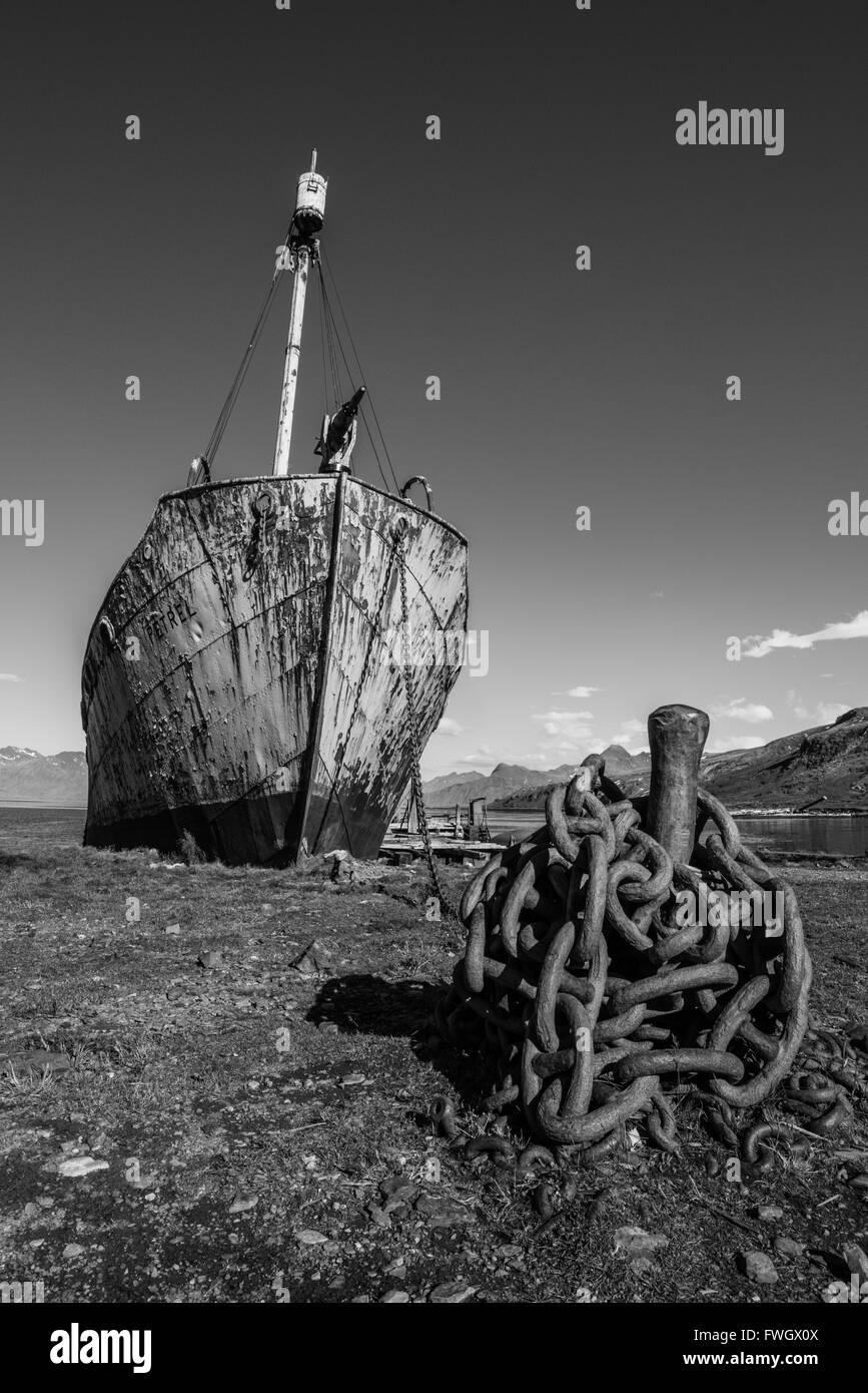 Mono whaler with harpoon beside rusty chain - Stock Image