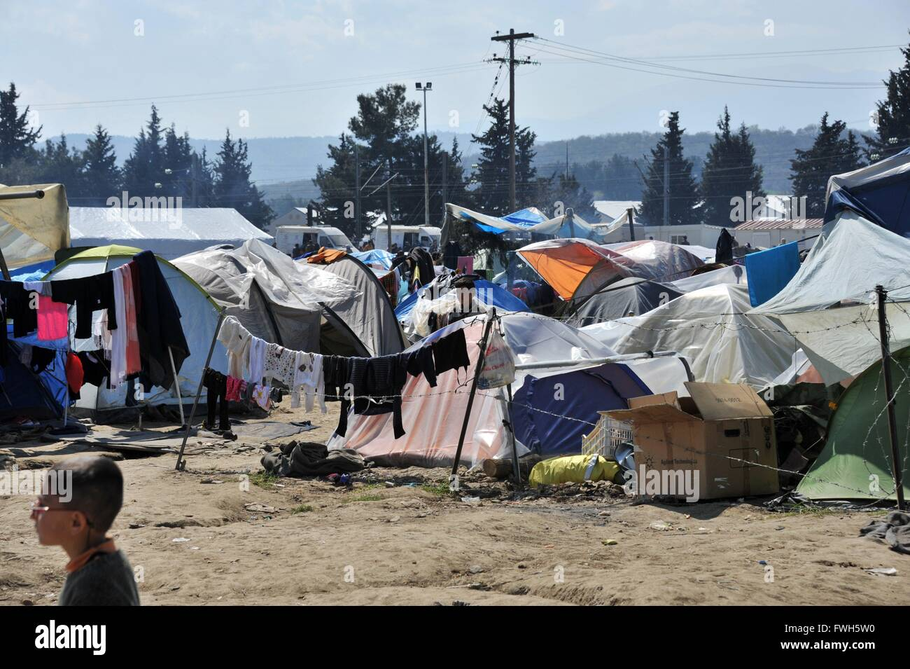 Shoulder to shoulder hundreds tents. On a barbed wire fence laundry is dried - 29 March 2016 - Stock Image