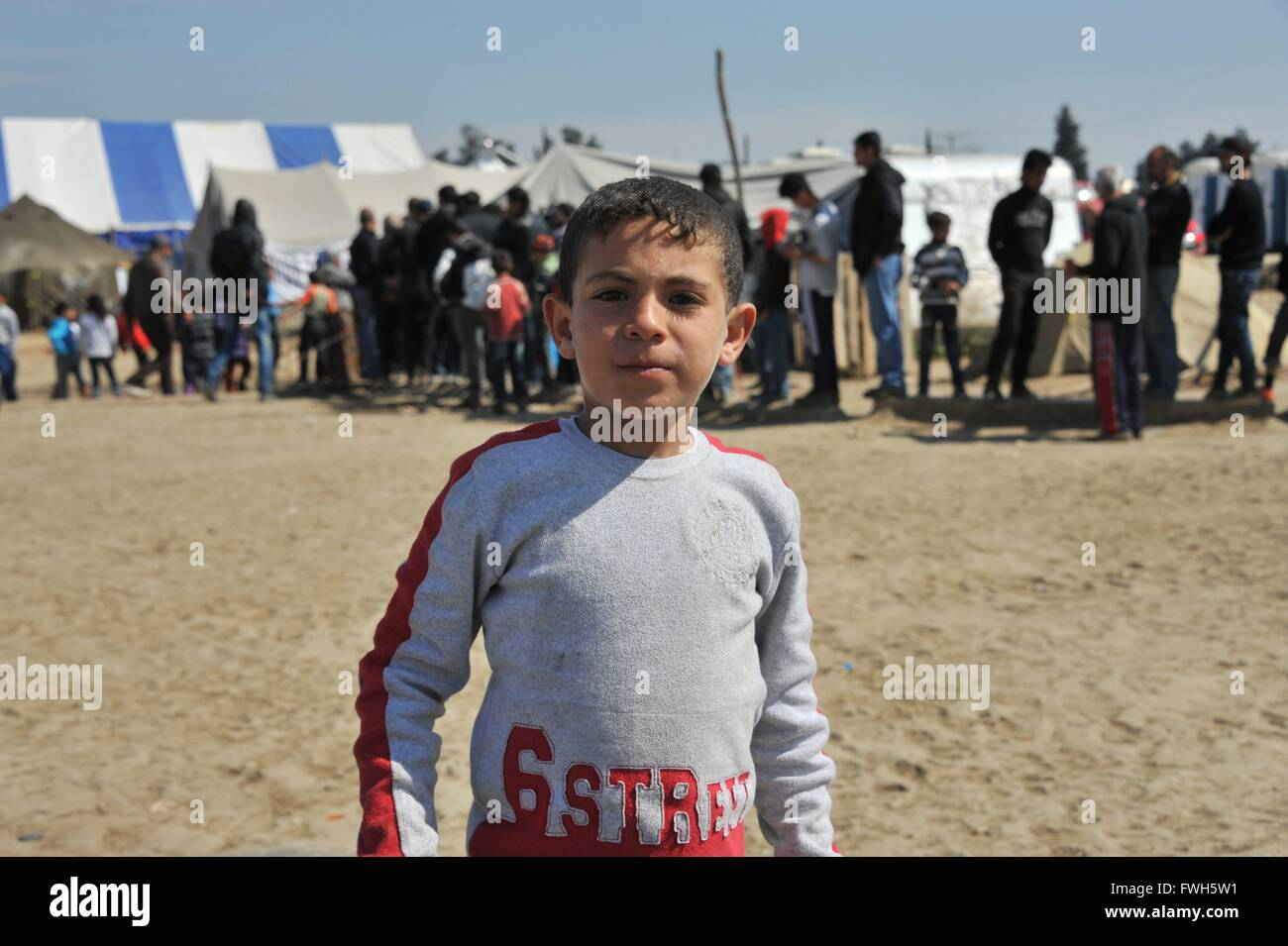Portrait of an Afghan boy. In the background, the 'Dari tea' tent - 29 March 2016 - Stock Image