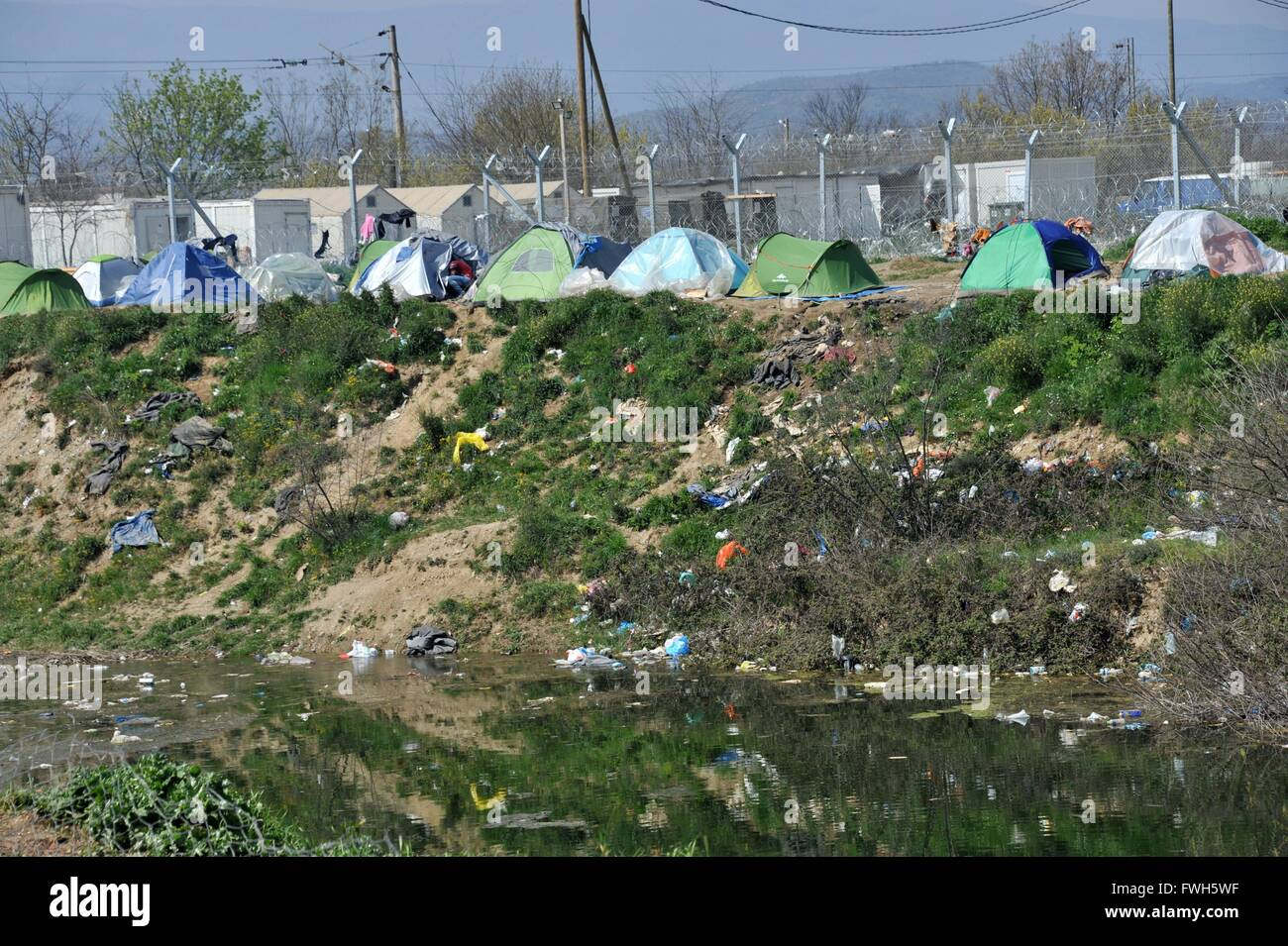 Tents on the other side of the river, up right on the border fence . Much garbage lying around - 29 March 2016 - Stock Image