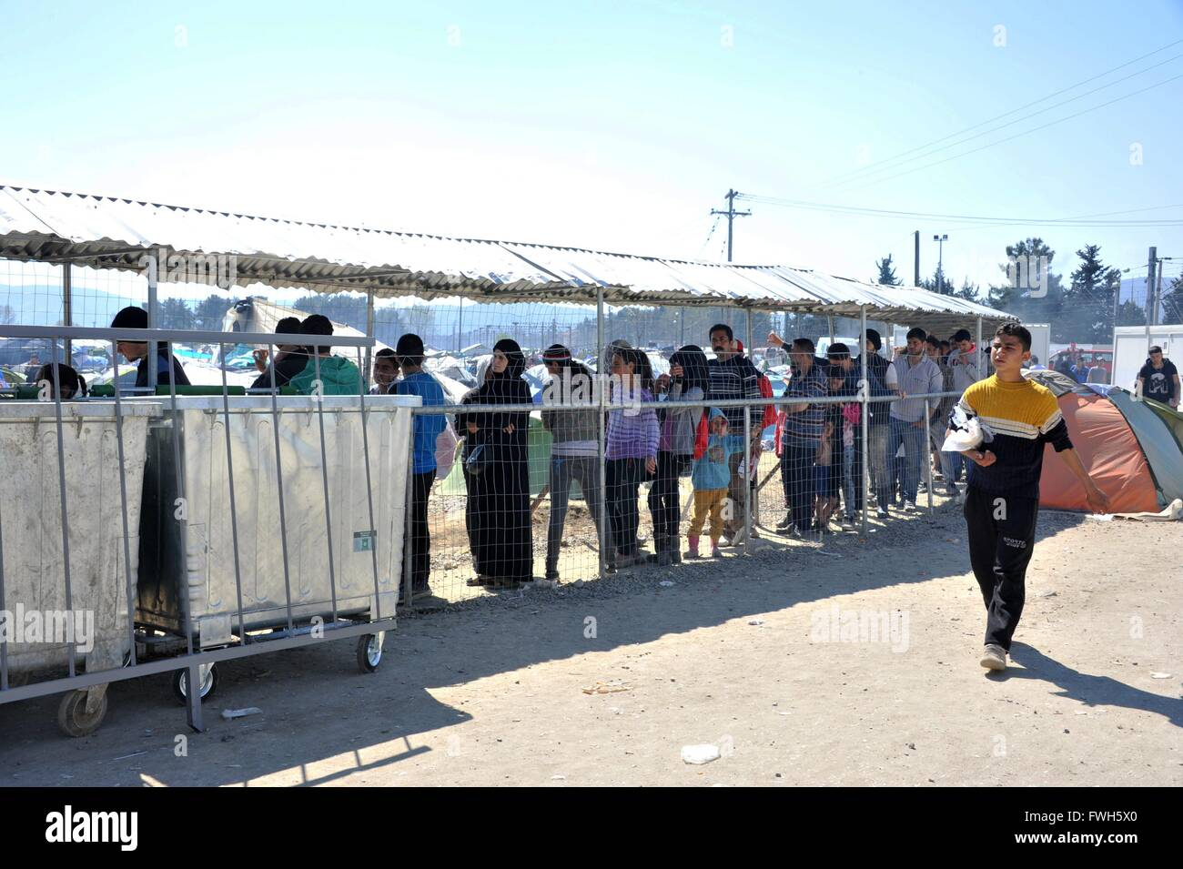 Two hours or more refugees are waiting in line to get food - 31 March 2016 - Stock Image