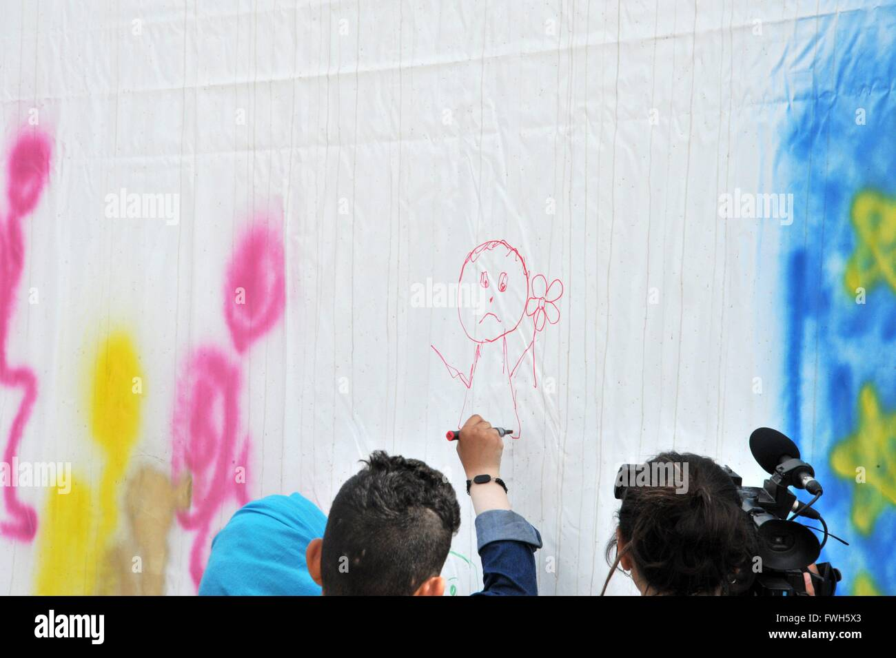Refugees spraying graffiti on a wall tent. Homeless, showing their way being sad - 1 April 2016 - Stock Image