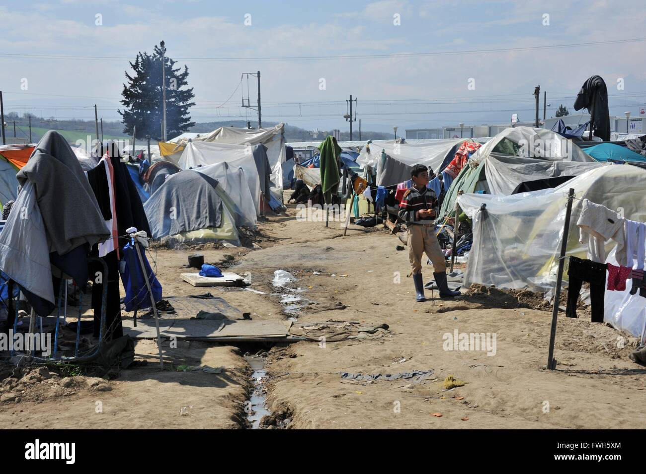 Living in tents. Clotheslines with laundry. A drainage ditch. One child and two veiled women in the background  - Stock Image