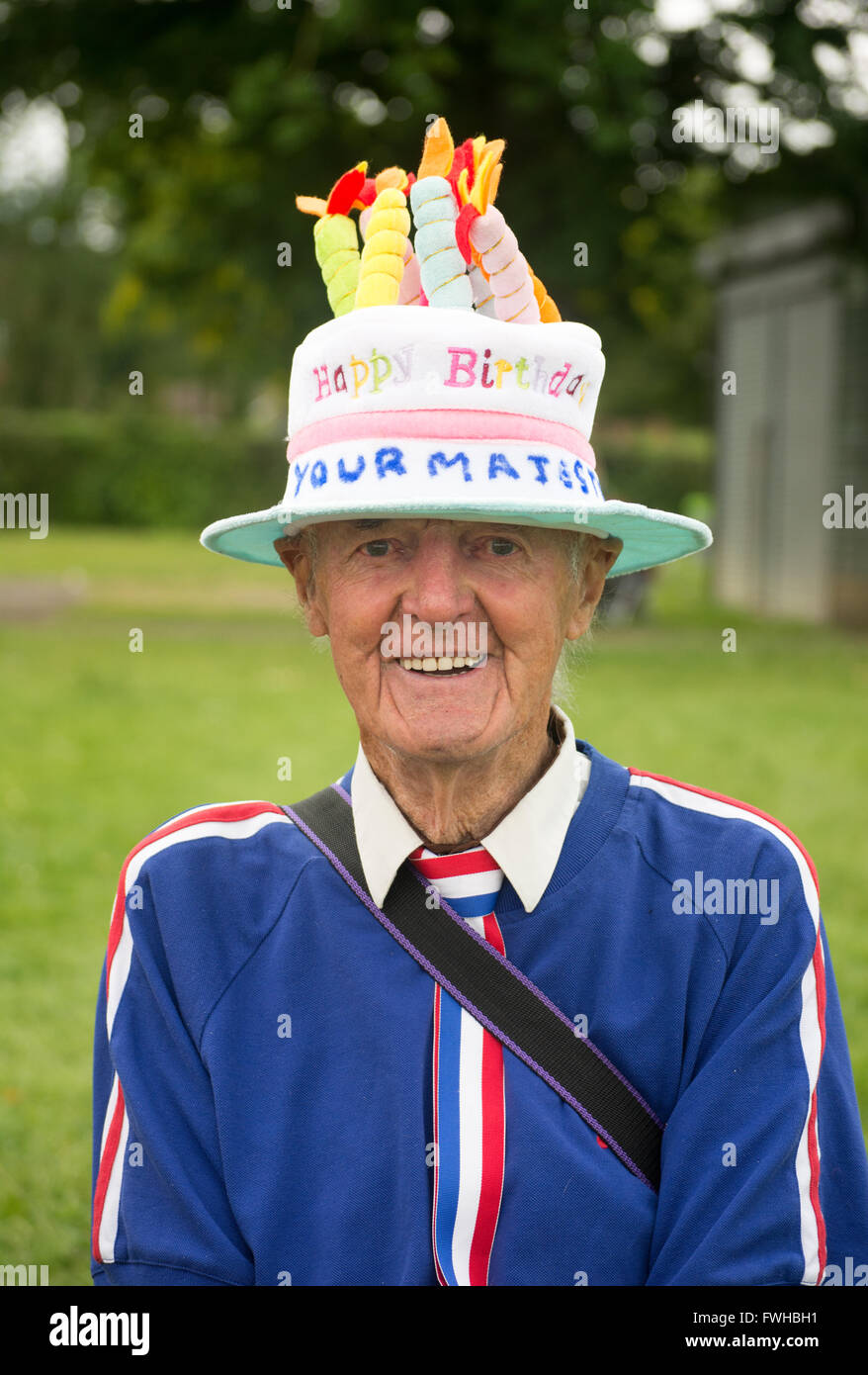 A Smiling Elderly Man Wearing Birthday Cake Hat With Candles On Top During The Queens 90th Celebrations In Fordingbridge Hampshire UK June