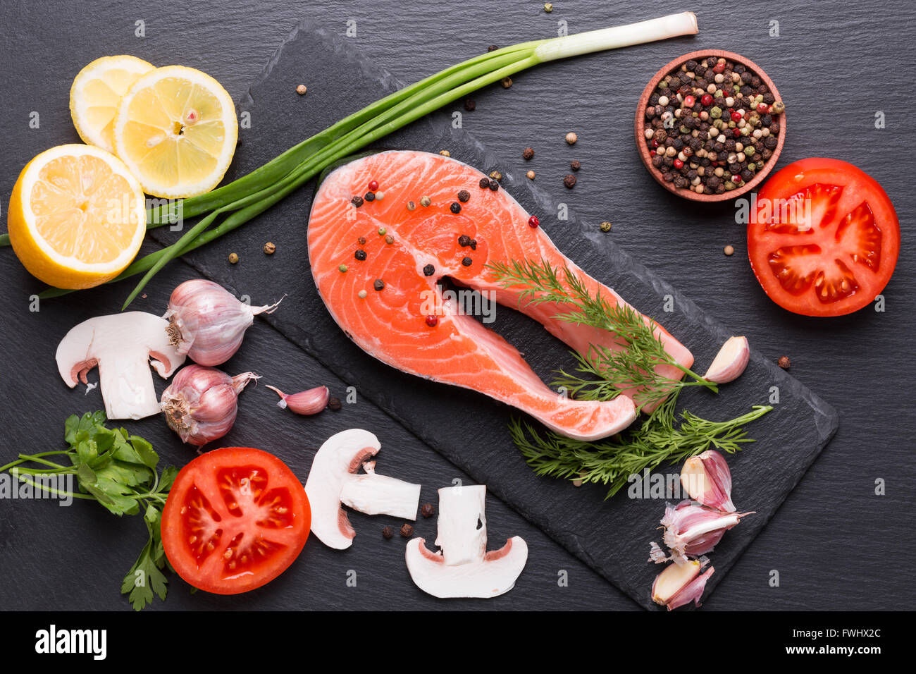 red fish steak with spices and vegetables on a slate table. - Stock Image