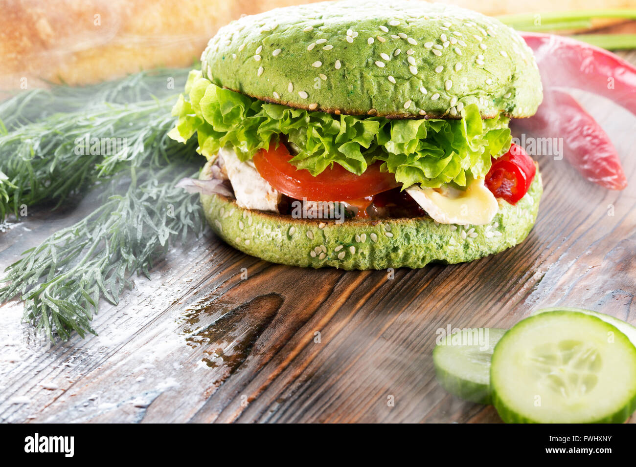 burger with green bun in light smoke on wooden background. - Stock Image
