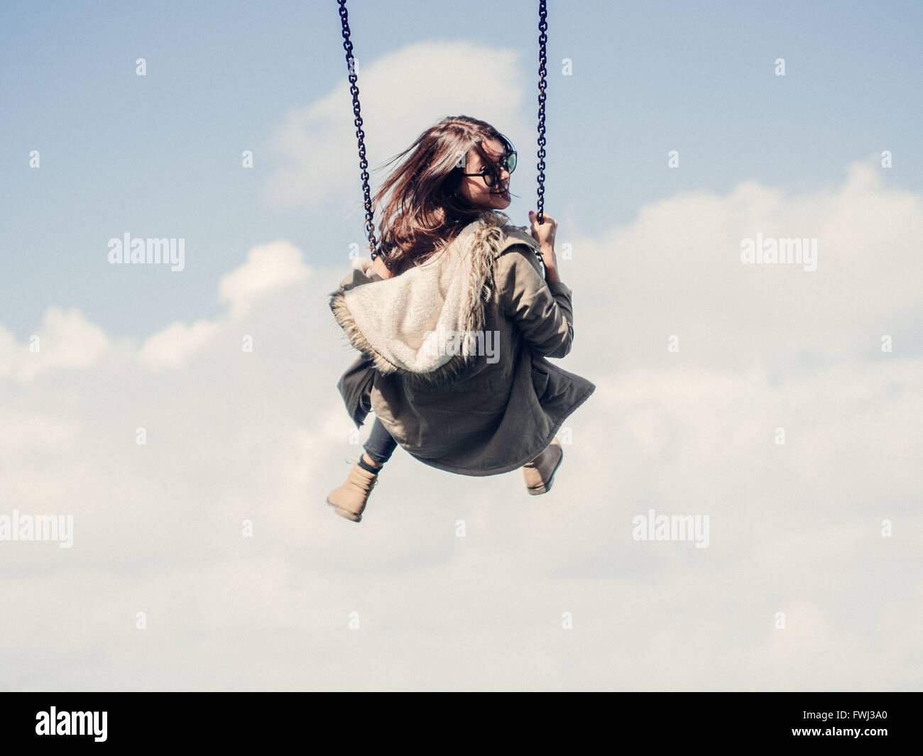 Low Angle View Of Woman On Swing Against Cloudy Sky - Stock Image