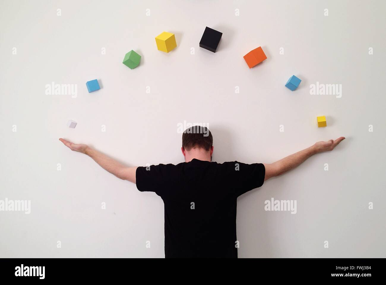 Rear View Of Man Stretching Arms On Wall With Colorful Cubes - Stock Image