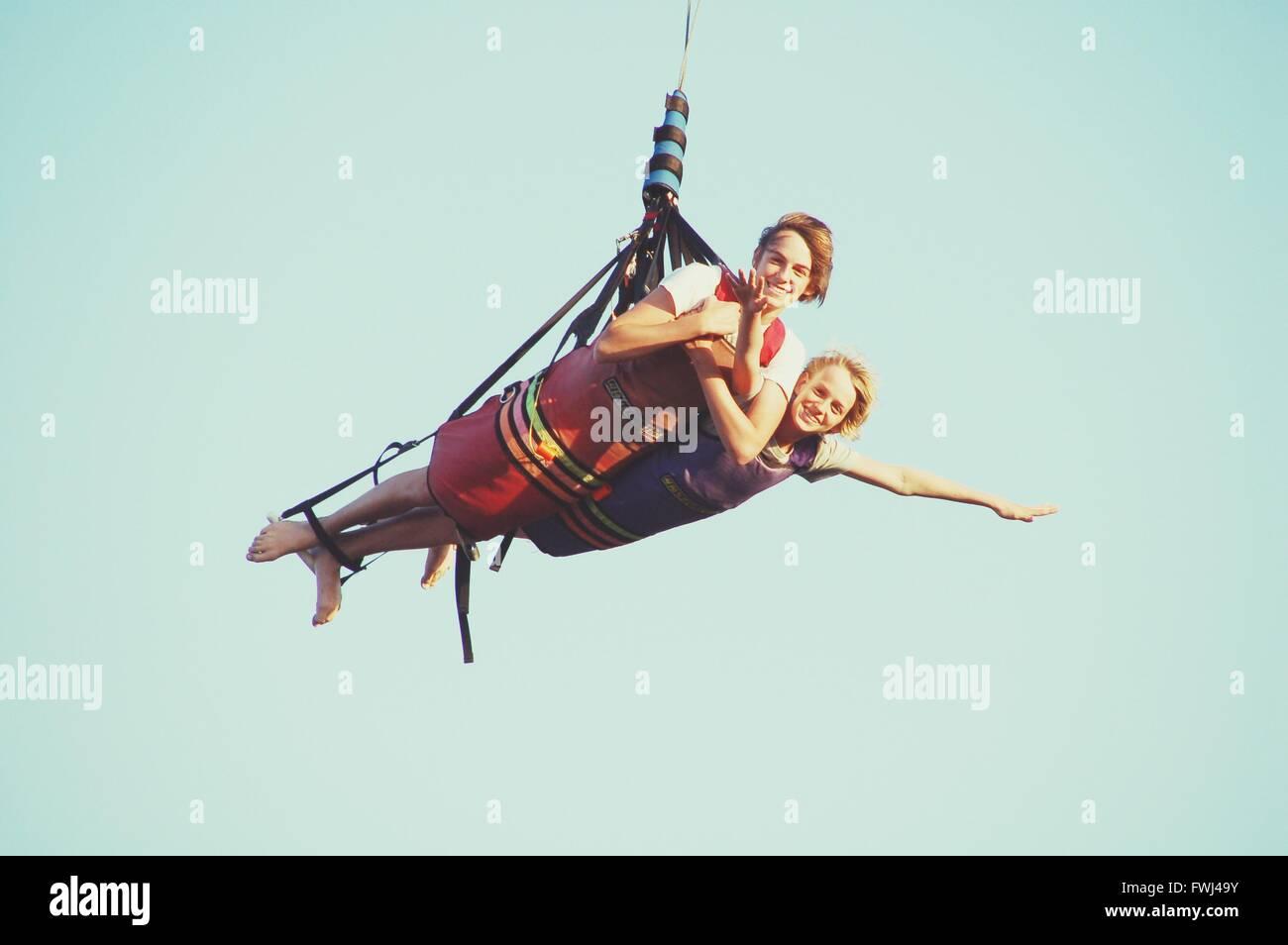 Low Angle View Of Couple Hang Gliding - Stock Image