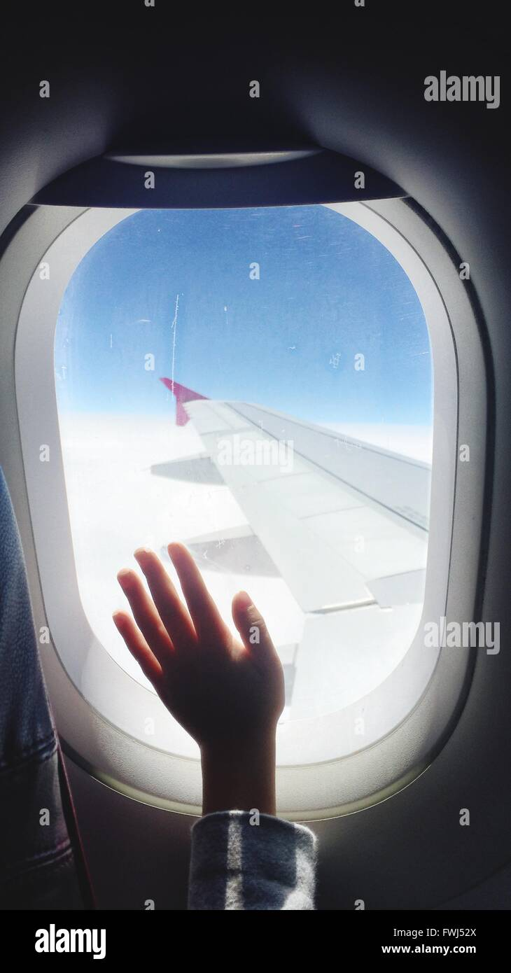 Cropped Image Of Hand On Airplane Window - Stock Image