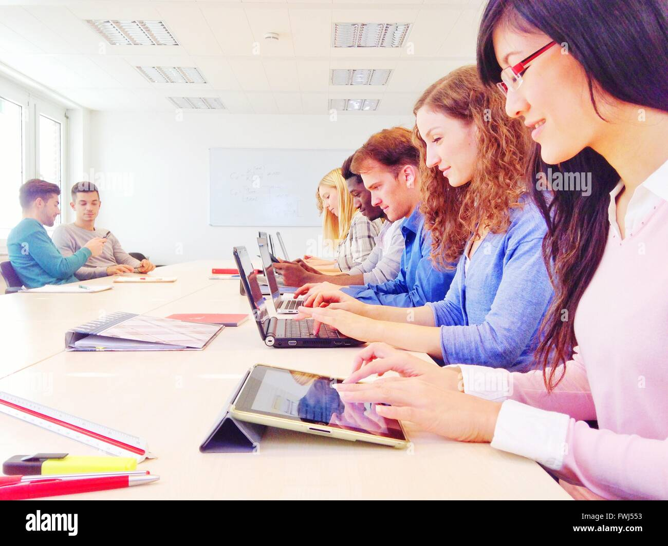 Business People Using Technologies At Conference Table - Stock Image