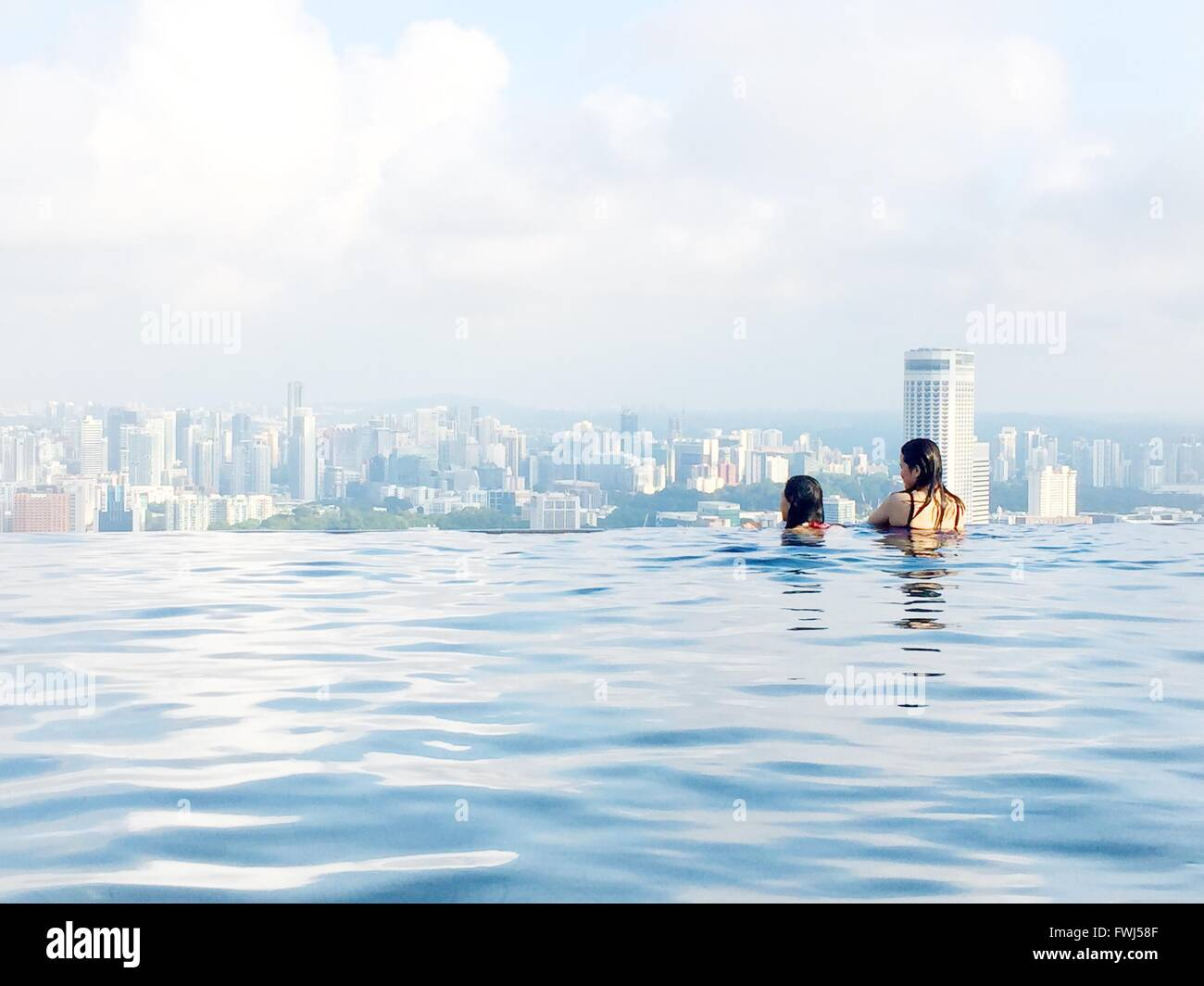 Women Looking At View From Infinity Pool At Marina Bay Sands - Stock Image