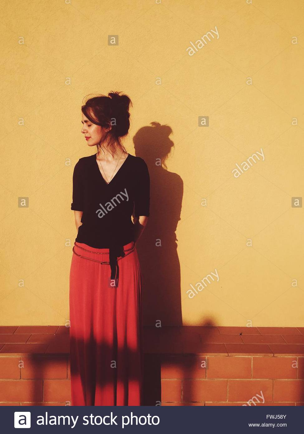 Woman With Eyes Closed Standing Against Wall - Stock Image