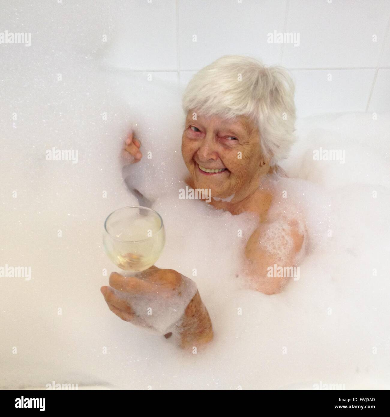 High Angle View Of Senior Woman In Bathtub With Bubbles Holding ...