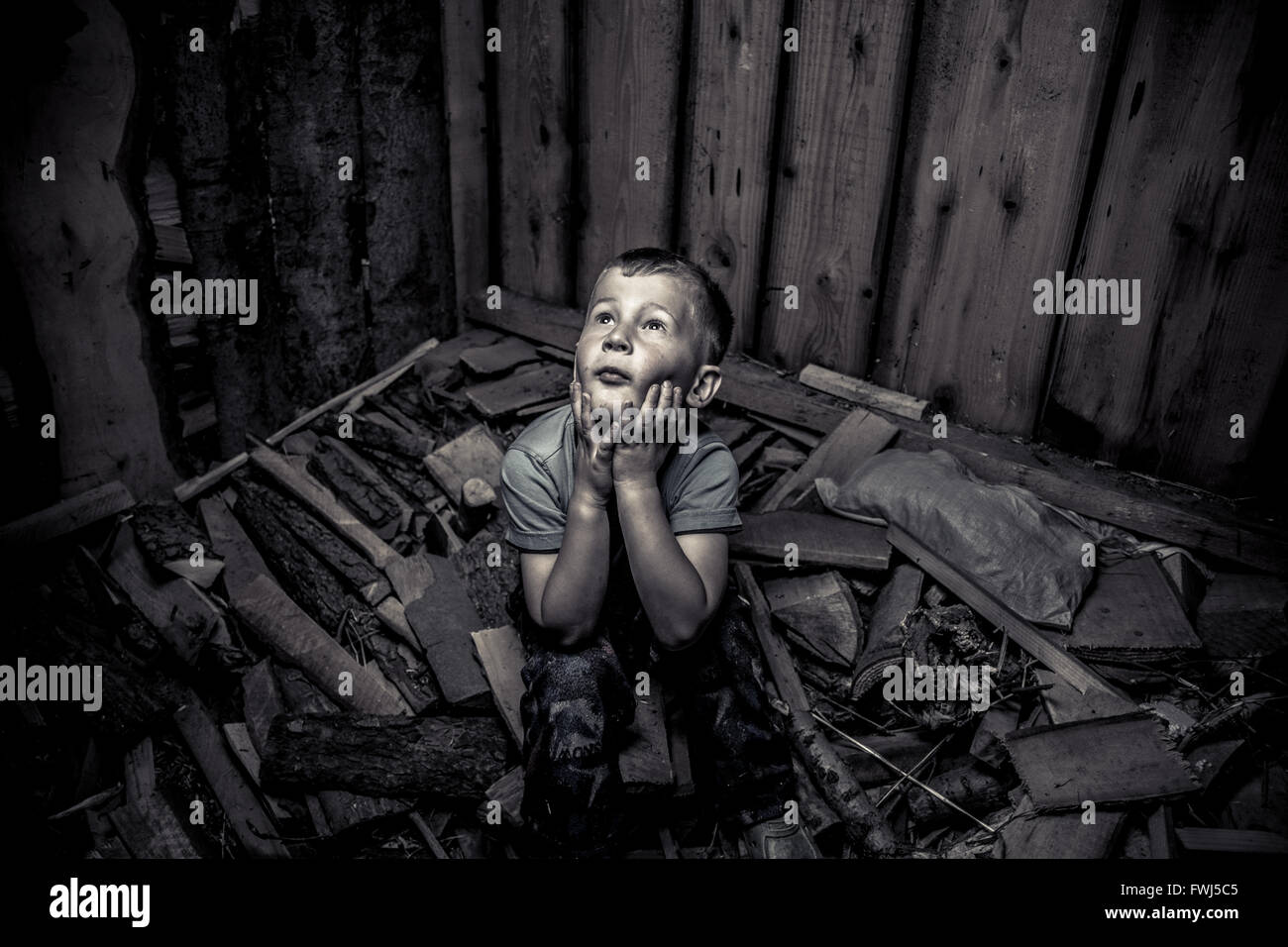 High Angle View Of Frightened Boy Looking Up In Abandoned Room - Stock Image