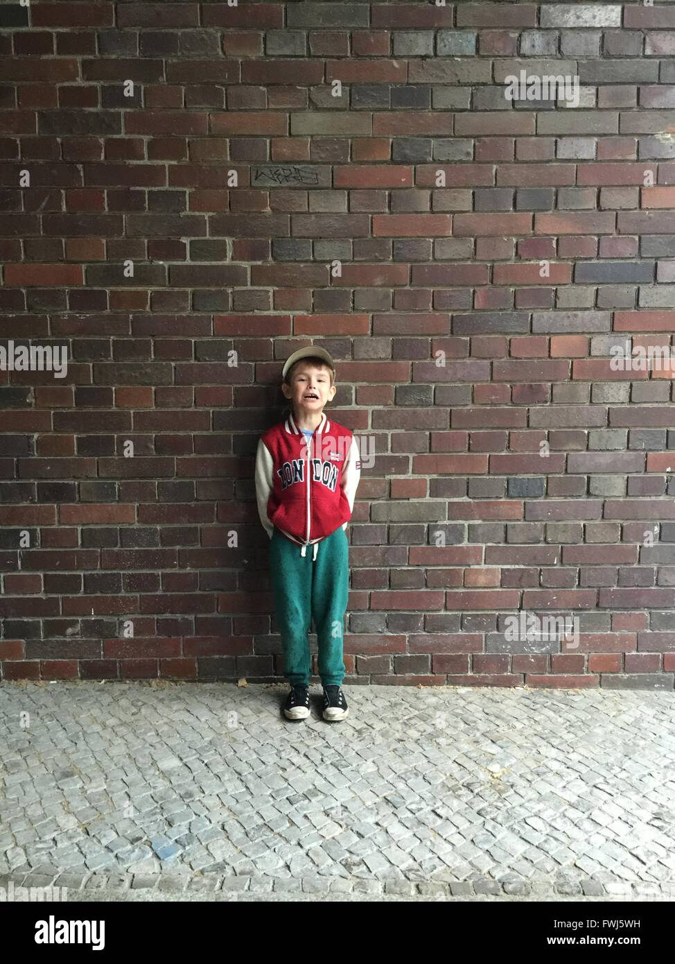Portrait Of Boy Crying While Standing Against Brick Wall - Stock Image