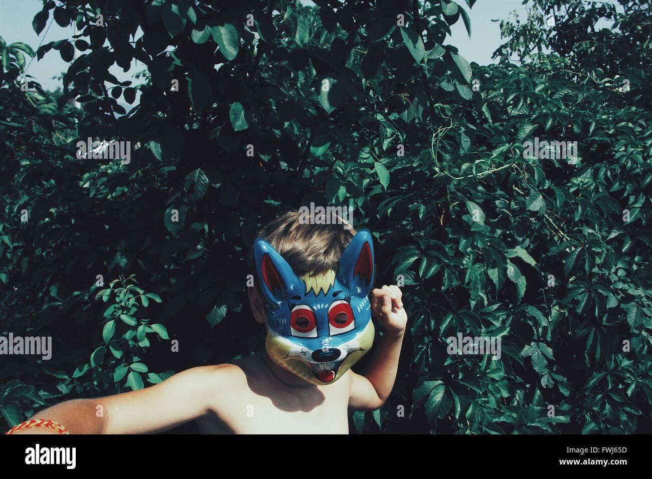 Shirtless Boy Wearing Fox Mask At Backyard - Stock Image