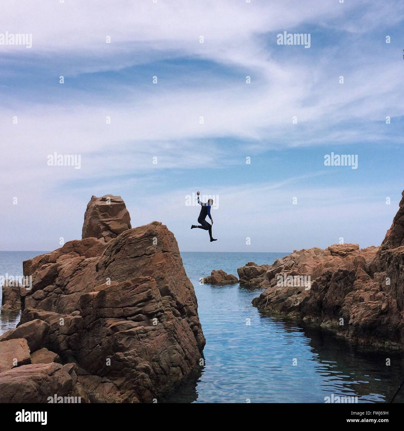 Man Jumping In Sea Against Cloudy Sky - Stock Image