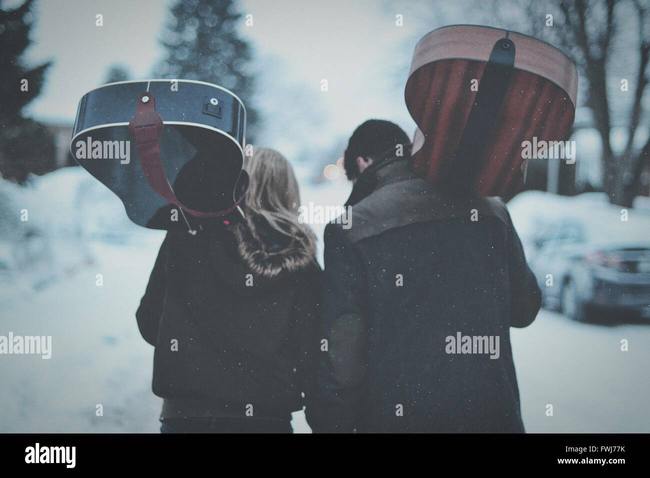 Rear View Of Friends Walking With Guitar Walking During Snowfall - Stock Image